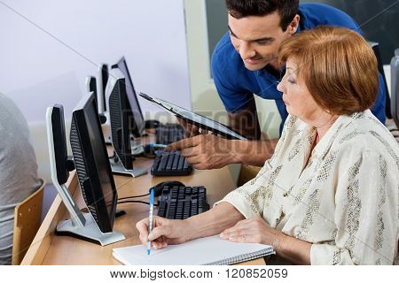 Computer Tutor Holding Clipboard While Senior Woman Writing Note