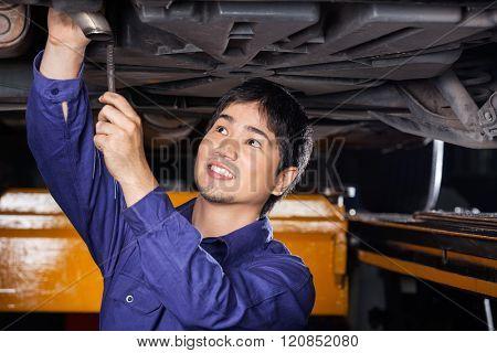 Mechanic Repairing Underneath Lifted Car