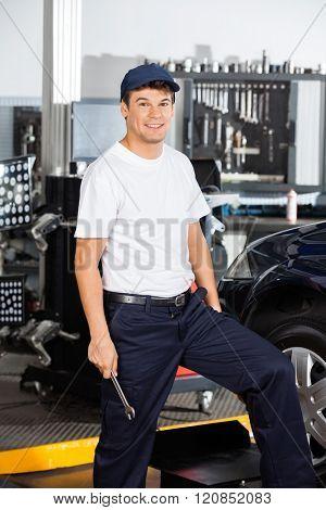 Smiling Male Mechanic In Garage
