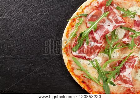 Pizza with prosciutto and mozzarella on stone table. Top view with copy space