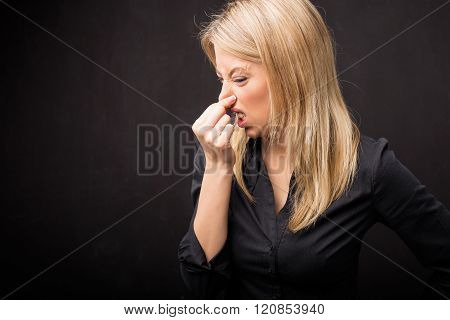 Woman holding her nose in disgust