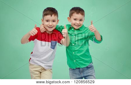 childhood,  school, education, friendship and people concept - happy smiling little boys showing thumbs up over green school chalk board background