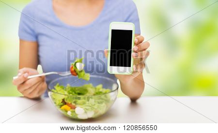 healthy eating, dieting, technology, food and people concept - close up of young woman with smartphone eating vegetable salad over green natural background