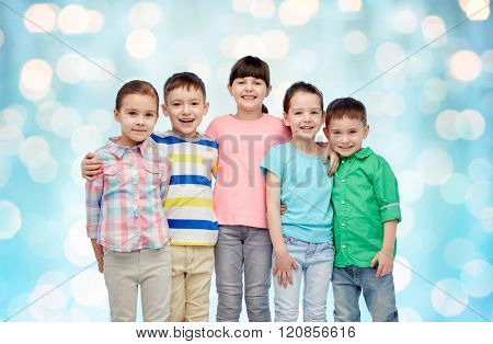 childhood, fashion, friendship and people concept - group of happy smiling little children hugging over blue holidays lights background