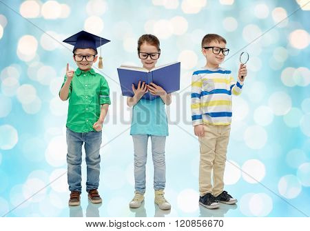 childhood, education, knowledge and people concept - happy little children in eyeglasses with book, magnifying glass and mortar board over blue holidays lights background