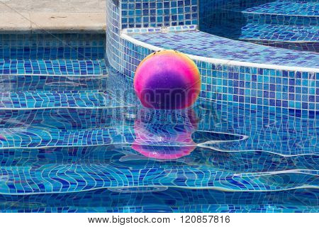 colored ball by the pool in the summer
