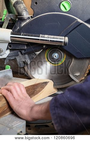 Close up of carpenter's hands using circular saw in his workshop