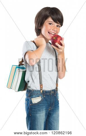 Closeup of smiling little boy eating red apple. Portrait of happy schoolboy holding the books and looking at camera. Cute boy with freckles isolated on white background. Scholar back to school.