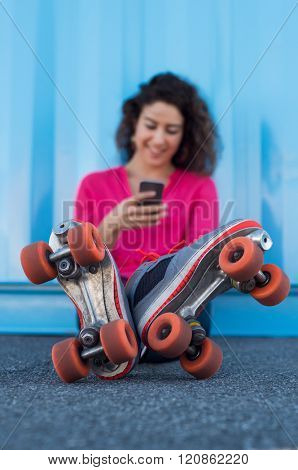 Woman sitting on ground wearing rollerskates holding a smartphone. Young woman reading a text message and smiling. Happy young woman sitting and wearing rollerskates while typing on smart phone.