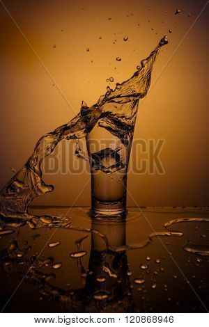 Exploding Glass cup with water shattering over orange background, crash and splashes ** Note: Visible grain at 100%, best at smaller sizes