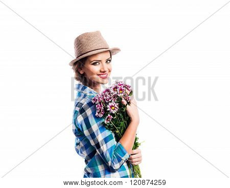 Woman in checked shirt holding bouquet of chrysanthemum flowers