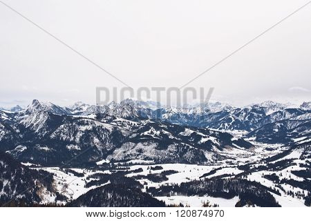 Large spread out mountain range covered with evergreen trees and patches of white snow under overcast skies
