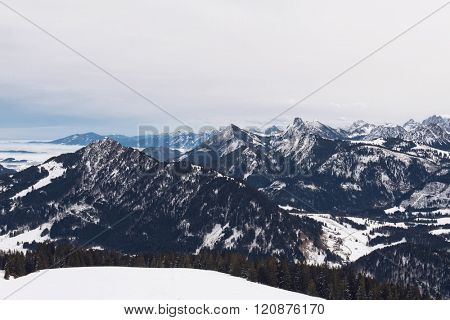 Panoramic view of rugged alpine peaks and valleys under snow in winter on a misty overcast cold day in an aerial overview from a plateau