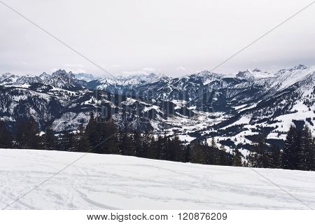 Panoramic view of snow covered alpine mountains with rugged peaks surrounding a forested valley on a cold grey winter day with snowy slope in the foreground