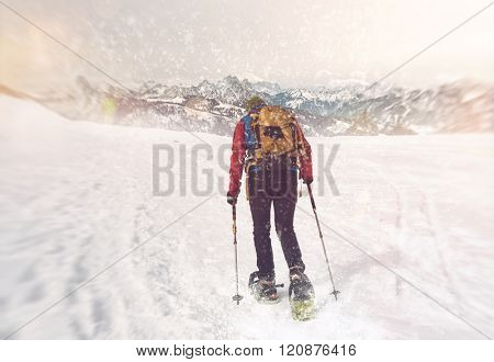 Single unidentifiable cross country snowshoe trekker with backpack and poles moving through snow storm in mountain landscape