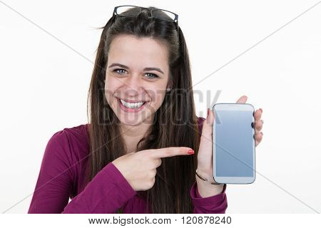 Cheerful Cute Woman Pointing Finger On Smartphone Screen Isolated On A White Background. Looking At