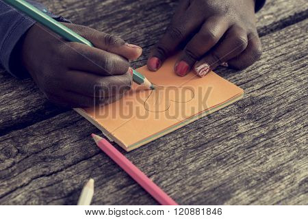 Closeup Of African-american Girl Drawing And Coloring A Heart Shape