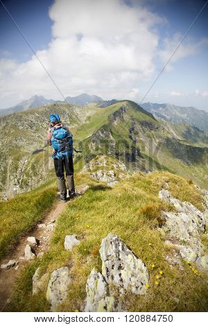 Hiker admiring view and taking photographs of high mountains