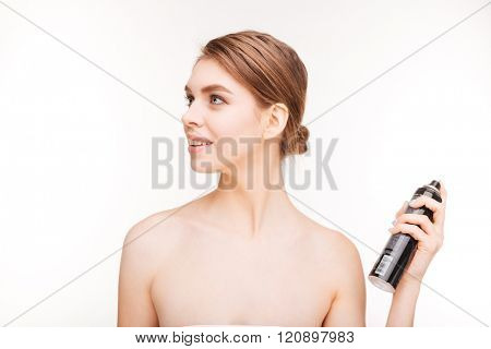 Beauty portrait of happy young woman applying hairspray on her hair over white background