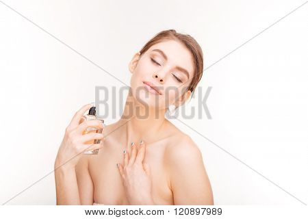 Beauty portrait of sensual young woman with closed eyes applying parfume on her neck over white background