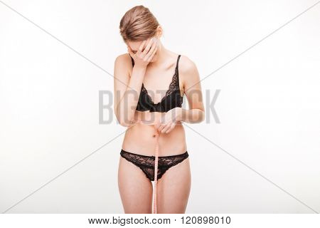 Depressed attractive young woman in black lingerie closed face by hand and measuring her waist over white background