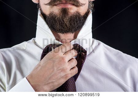 Elegant Bearded man in white shirt trying on his tie.