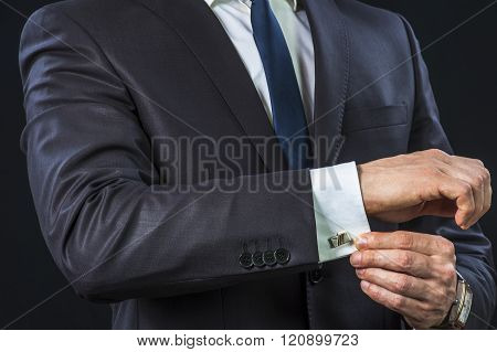 Elegant businessman correcting his cufflinks and sleeve.
