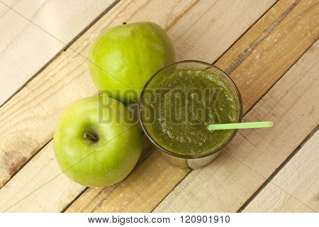 A glass of apple smoothie with a drinking straw and two apples, on a wooden background