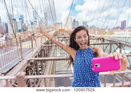 Happy selfie tourist woman taking fun self-portrait picture with smart phone app on Brooklyn Brige, New York City, Manhattan, USA. Asian woman posing with smartphone for social media.