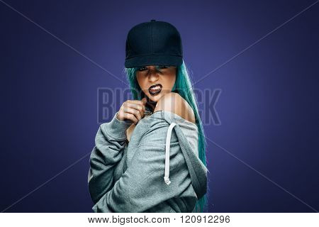Sexy hip hop woman in hoodie and cap