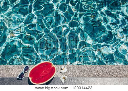 Watermelon, sunglasses and spa flowers near the blue pool. Tropical fruit diet. Summer holiday idyllic.