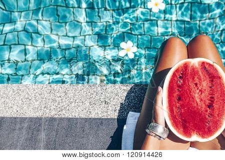Girl holding watermelon in the blue pool, slim legs, instagram style. Tropical fruit diet. Summer holiday idyllic.