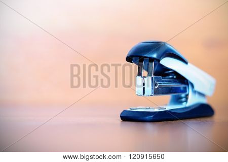 One stapler on blurred wooden background. Stapler on table.
