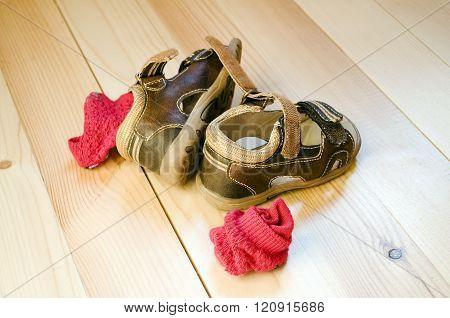 Children's sandals and socks on wooden floor