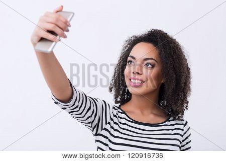 Pleasant mulatto woman making selfies