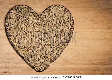 Fennel dill seeds heart shaped on wooden board