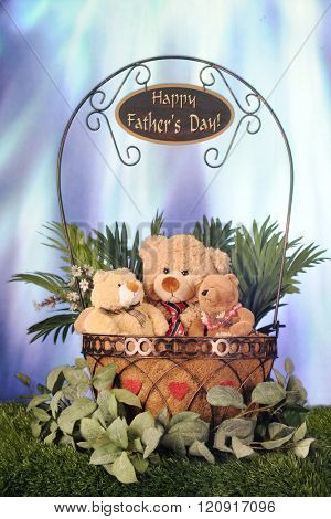 Toy father, son and daughter bears sitting in a wire basket of foliage.  A Happy Father's Day sign dangles from the basket's handle while a bright blue light shines down on it.