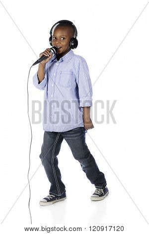 A handsome preteen boy wearing earphones as he makes his announcement over a mike.  On a white background.