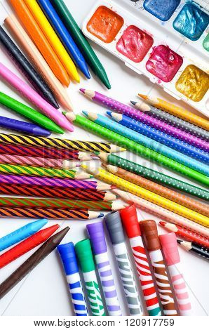 Colored Pencils, Crayons, Markers And Paints On White Background