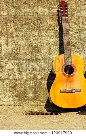 Acoustic Guitar Outdoor On Wall Background