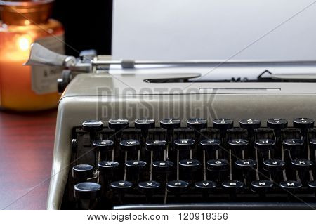 Old typewriter sitting on a table by candlelight