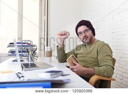 young happy hipster businessman working from his home office as freelancer wearing casual beanie jeans and glasses smiling in self employed business model success