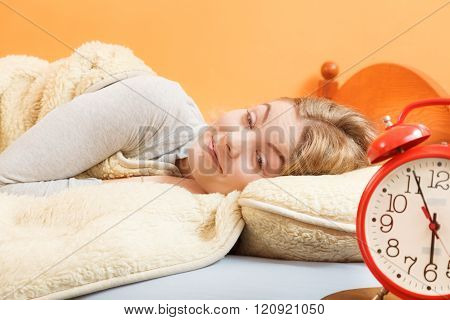 Woman Rest In Bed Under Blanket With Alarm Clock.