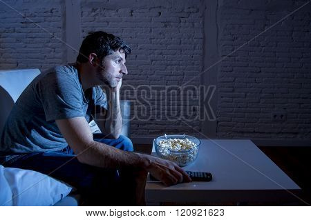 young television addict man sitting on home sofa watching TV eating popcorn using remote control looking bored and tired zapping foe another movie sitcom or live sport at night