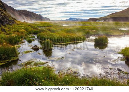 Hot steam over the source of the thermal waters.  White nights in Iceland. Sunrise Park Landmannalaugar
