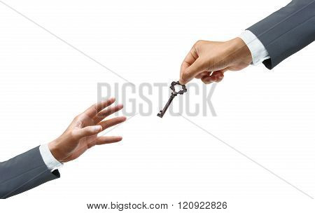 hand of a businessman giving a key to many hopeless hands - giving help, opportunity, success concept