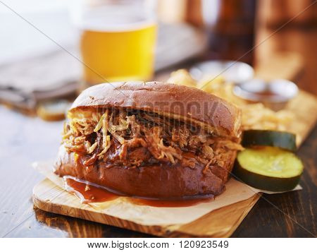 pulled pork sandwich on wooden tray with pickles and beer