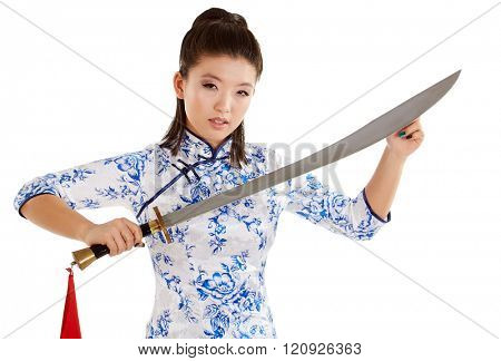 young beautiful Japanese woman in kimono looking aggressively at camera and holding katana sword