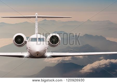 Travel by aircraft. Airplane fly over clouds and Alps mountain on down. Front view of a big passenge