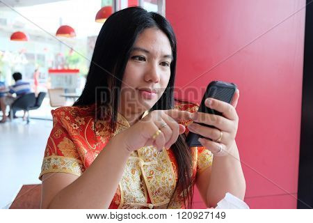 Woman In Red And Golden Chinese Costume Using Mobile Phone